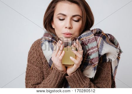 Photo of sick young woman in sweater and scarf holding glass with medicine and looking at glass. Isolated over gray background.
