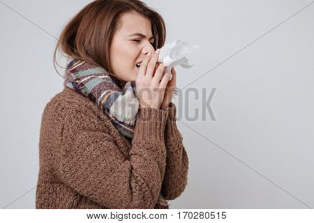 Photo of sick young woman in sweater and scarf standing with napkin isolated over gray background.