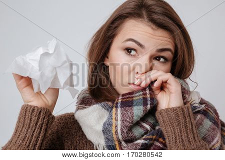 Picture of sick young lady in sweater and scarf standing with napkin isolated over gray background.