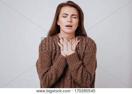 Image of sick young woman dressed in sweater standing isolated over gray background and touching her neck.