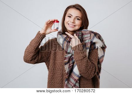 Image of sick young lady in sweater and scarf holding medicine pills. Isolated over gray background.