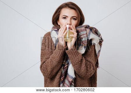 Image of sick young lady in sweater and scarf holding glass with medicine and looking at camera. Isolated over gray background.