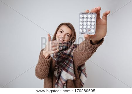 Photo of sick young lady in sweater and scarf showing to camera medicine pills. Isolated over gray background.