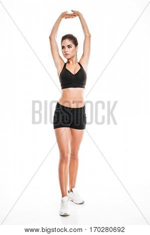 Full length of cute graceful young woman athlete standing and stretching hands over white background