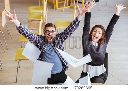 Top view of happy cheerful students having fun in library by throwing papers