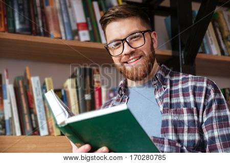 Portrait of a smiling young male student in eyeglasses holding open book and looking at camera at the library