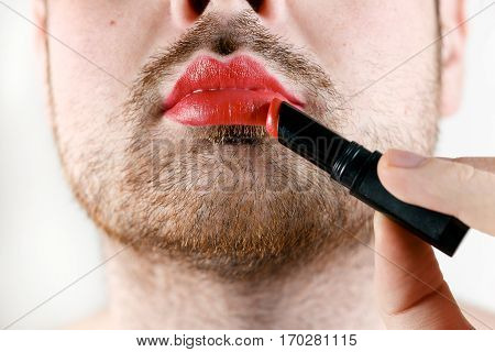 Bearded Man Transvestite Makes Up Lips with Lipstick.