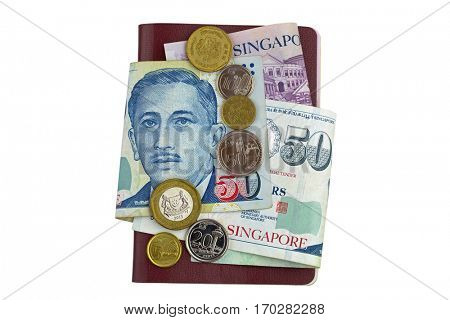 Singapore dollar banknote (SGD) and coins on red brown Passport isolated on white background