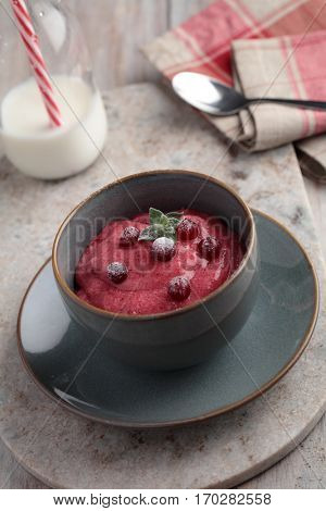 Whipped cranberry semolina porridge vispipuuro with fresh berries on a rustic table