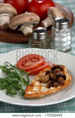 Grilled chicken breast with roasted mushrooms, rocket salad, and tomato