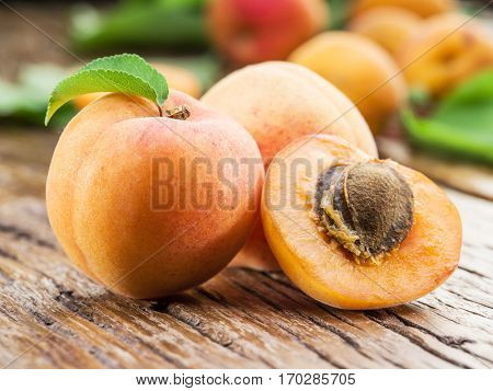 Apricots and its cross-section on the old wooden table.