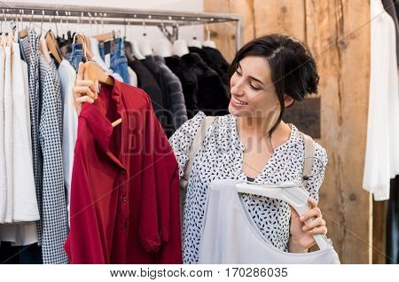 Happy young woman choosing between two dresses in clothing shop. Smiling girl trying to select a dress in a clothing store during sales. Beautiful woman choosing the shirts in the store.