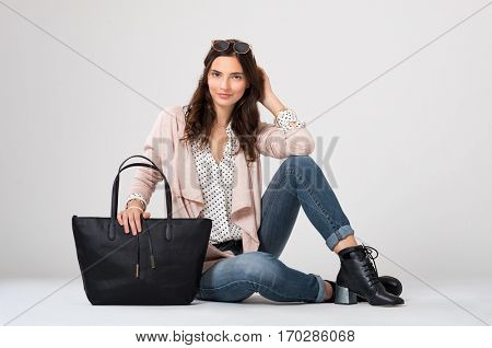 Cool young woman sitting down isolated on grey background. Young fashion woman looking at camera with trendy shopping bag. Stylish girl in casual clothes with accessory smiling.