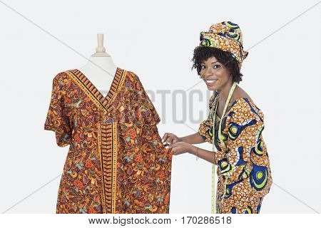 Portrait of an African American female fashion designer working on dashiki over gray background