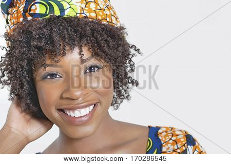 Close-up portrait of an African American woman smiling over gray background