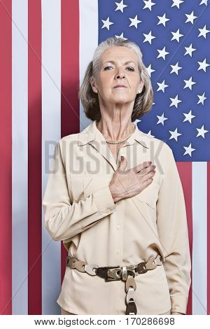 Portrait of senior woman with hand over heart against American flag