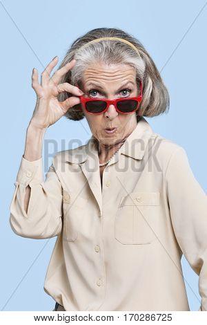 Portrait of senior woman wearing sunglasses against blue background