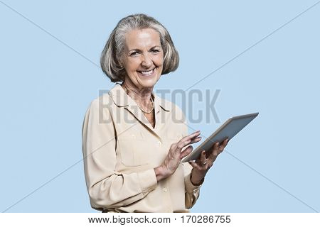 Portrait of senior woman using tablet PC against blue background