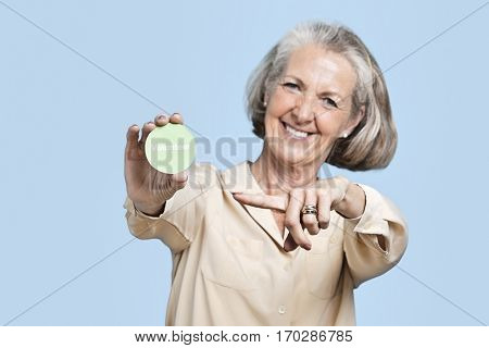 Portrait of senior woman holding volunteer badge against blue background