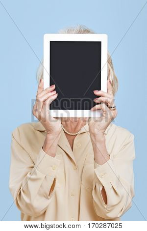 Senior woman holding tablet PC in front of her face against blue background