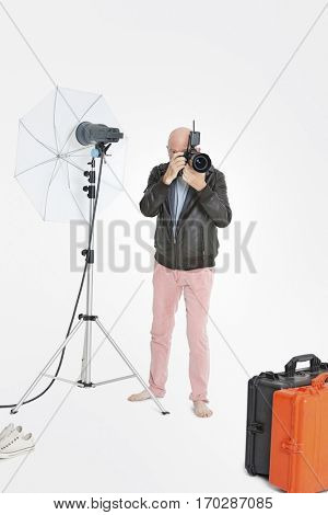 Senior photographer taking a photograph in studio