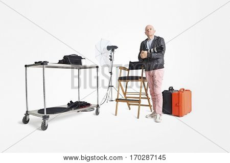 Portrait of senior man with camera and equipments standing in photographer's studio