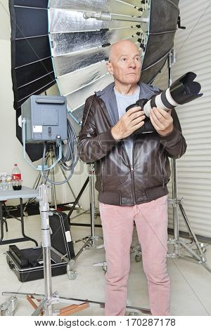 Front view of senior man with camera and equipments in photographer's studio
