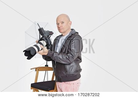 Senior photographer holding camera in studio