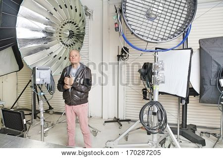 Senior photographer with camera and light reflectors in studio
