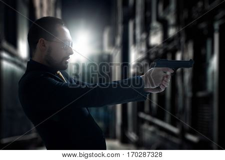 Gangster with gun in ghetto at night