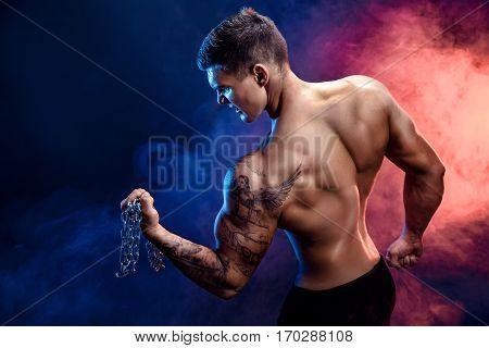 Closeup of a handsome power athletic man bodybuilder doing exercises with chain. Fitness muscular body on dark background. Perfect male. Awesome bodybuilder, tattoo, posing.