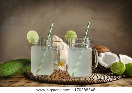 Two mason jars with coconut water on straw mat