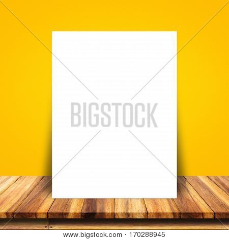 Blank white paper poster lean at yellow wall and wood table. For text input or according to your design.