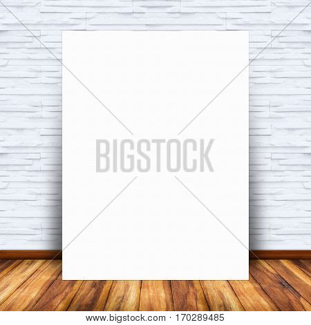 Blank white paper poster lean at brick wall and wood floor. For text input or according to your design.