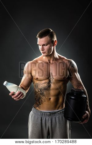 milk bottle in the hands of a sports person, healthy man with the proper way of life.tattoo