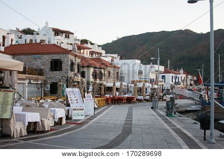 MARMARIS TURKEY - SEPTEMBER 11: Outdoor cafe and restaurtnas on sea-front street of Marmaris with mountains on background