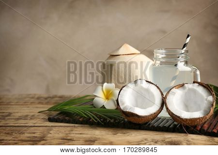 Fresh nuts and mason jar with coconut water on bamboo mat