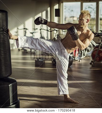 Shirtless handsome muscular young man in gym doing kick against punching bag, wearing boxing gloves