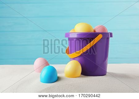 Easter eggs with sand and pail, on wooden blue background