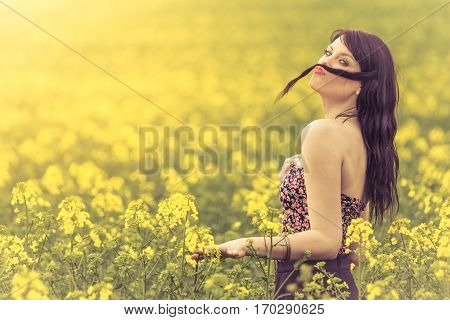 Funny beautiful spring girl with hair moustache in yellow meadow. Attractive happy young girl enjoying the warm summer sun and her health in a wide green and yellow meadow. Part of series.