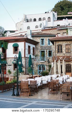 MARMARIS TURKEY - SEPTEMBER 11: Outdoor restaurants on old streets of Marmaris with wooden chairs and stone buildings on background