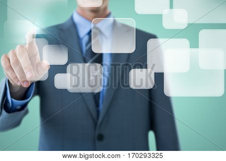 Well dressed businessman pointing against green background