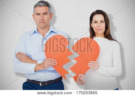 Portrait of couple holding broken heart shape paper against grey