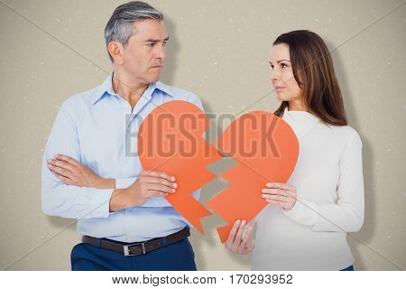 Couple holding broken heart shape paper against grey