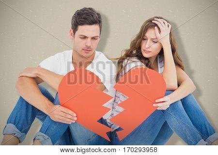 Young couple sitting on floor with broken heart shape paper against cream