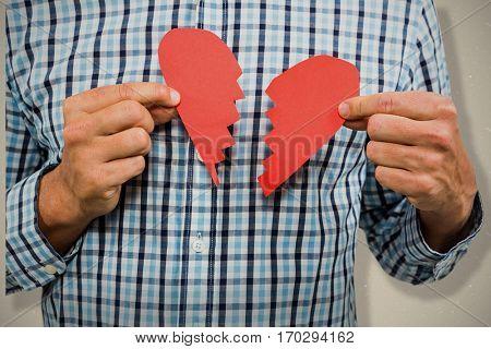 Sad man with broken heart against grey