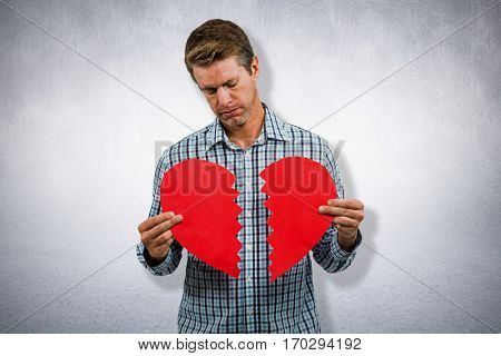 Sad man holding a broken card against white wall