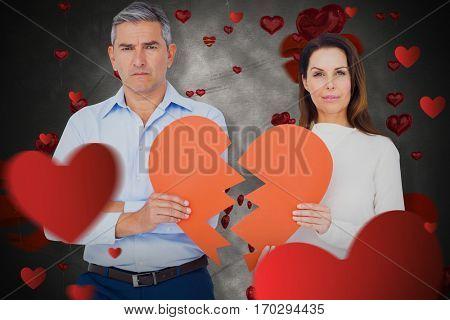 Portrait of couple holding broken heart shape paper against love heart pattern