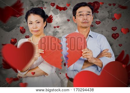 Couple holding broken heart against love heart pattern