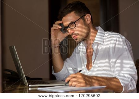 Pensive man working, attractive male sitting at table